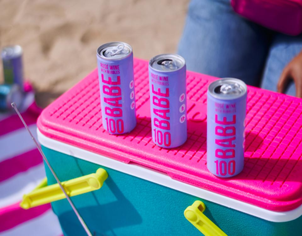 three purple canned beverages on a brightly colored cooler at the beach