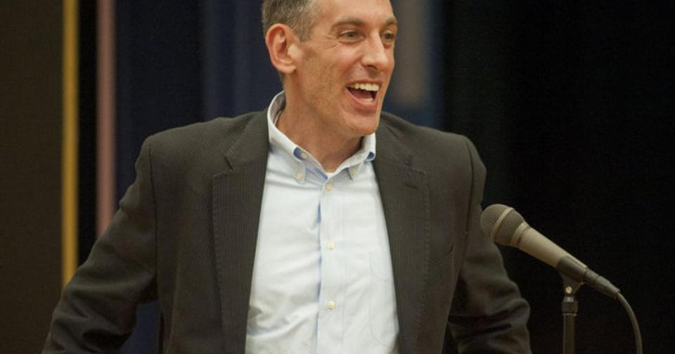 a man smiles wearing a gray suit and light blue button down shirt at a podium