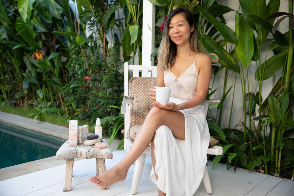 Wyld skincare line founder Joy Yap sits next to her product line with a cup of tea.