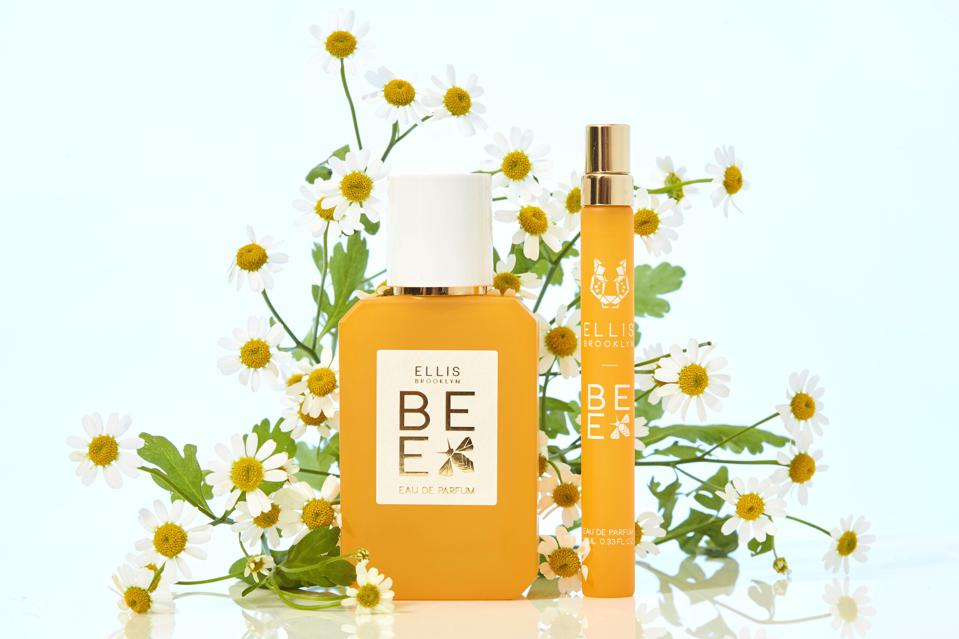 A bottle and tube of Ellis Brooklyn Bee Eau de Parfum against a background of flowers.