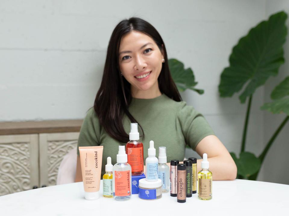 Founder Priscilla Thai sits at a table with a selection of Cocokind products.