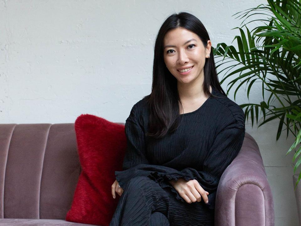 Cocokind founder Priscilla Thai sits on a velvet purple couch.