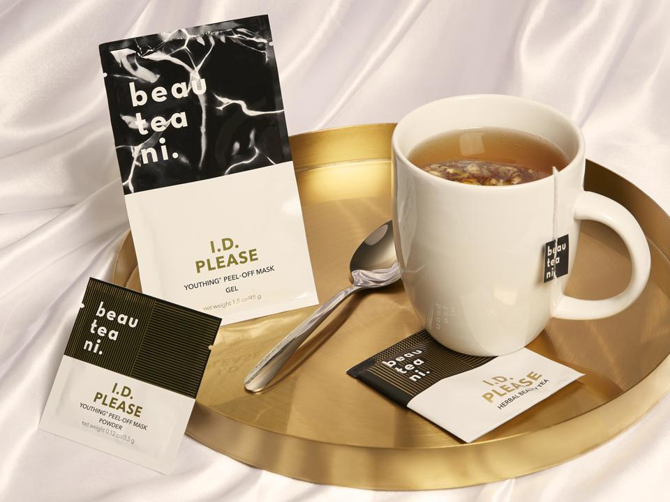 A cup of tea sits on a gold platter with Beauteani face masks and tea bags.