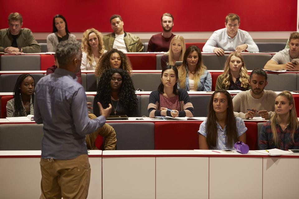 Back view of man presenting to students at a lecture