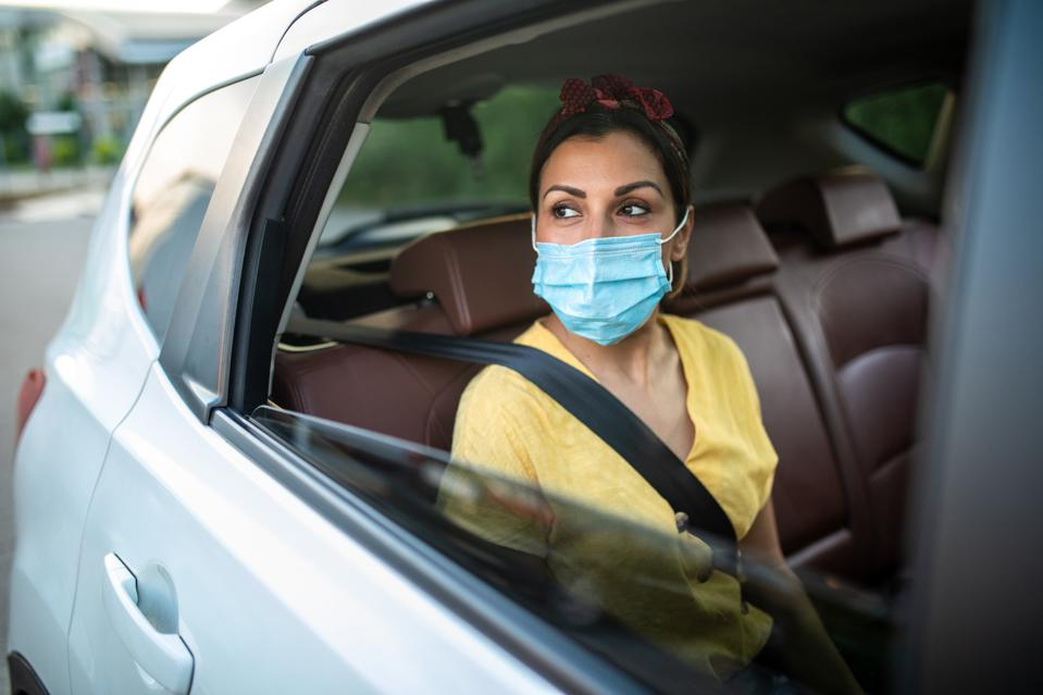 Woman with protective face mask, sitting on back seat of car, looking through the window and enjoying a ride