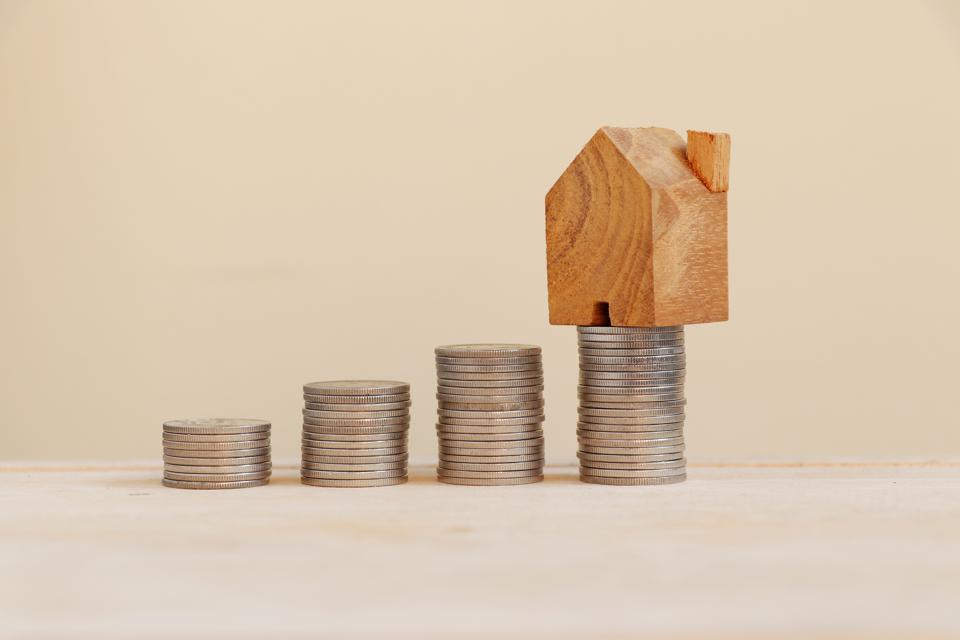 Coins are arranged in bars graph with wooden home model on top.