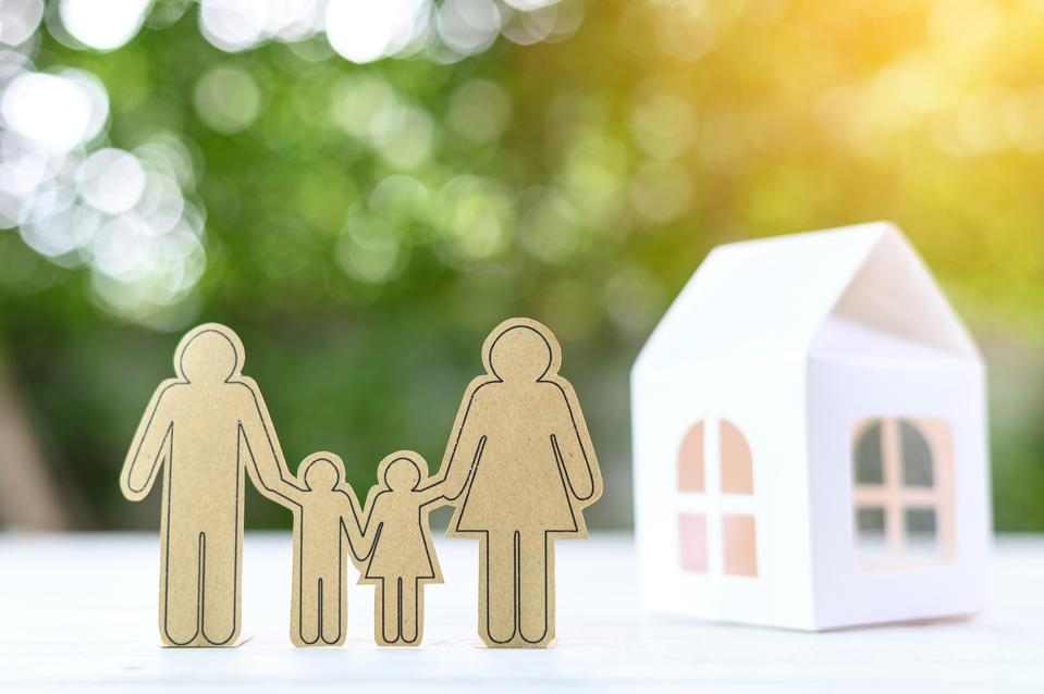 Concept of Family and house. Small paper model of house and family on blurred background