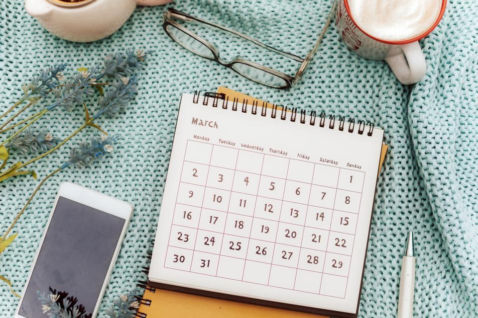 March calendar  in feminine workspace with lavender flowers, coffee , eyeglasses and pen