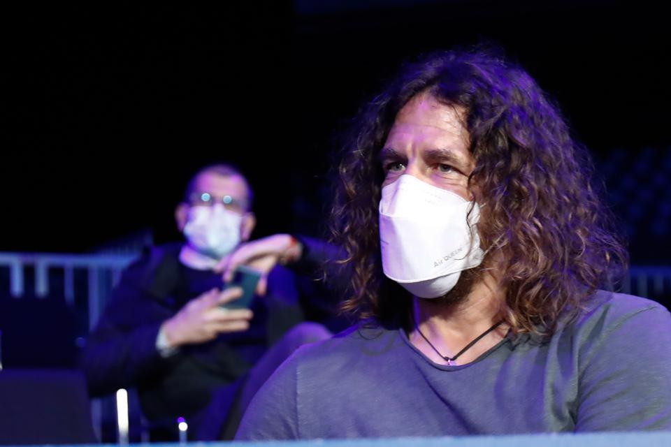 Carles Puyol sits indoors while wearing a white face mask.