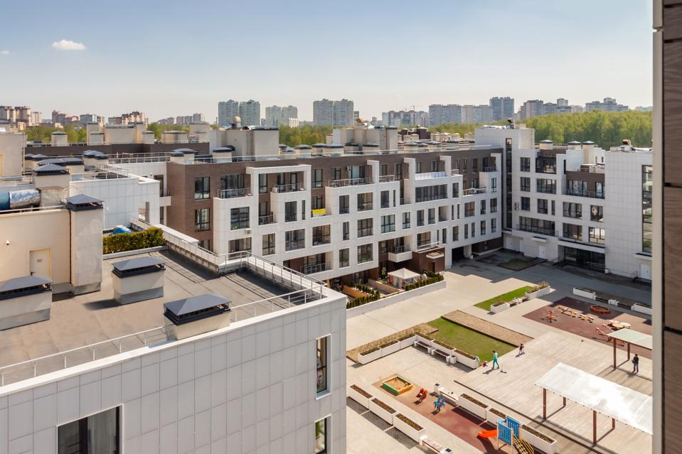 house building exterior with flat roof and playground for children mixed-use urban multi-family residential district area development sunny day