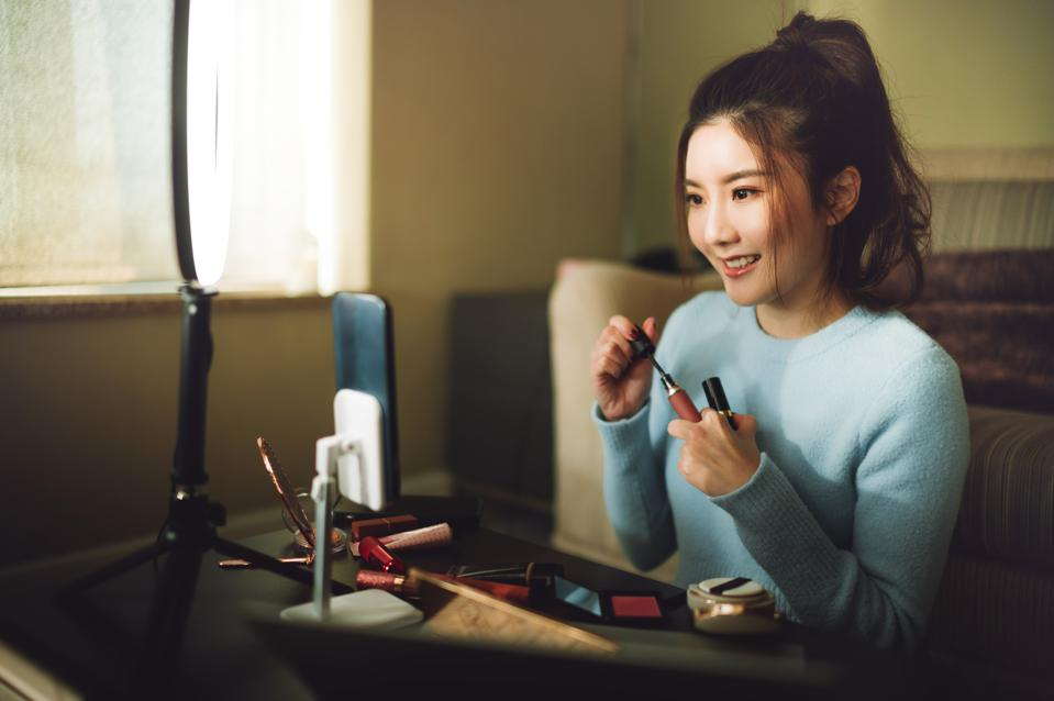 Young cheerful Asian woman doing live streaming for social media and Internet