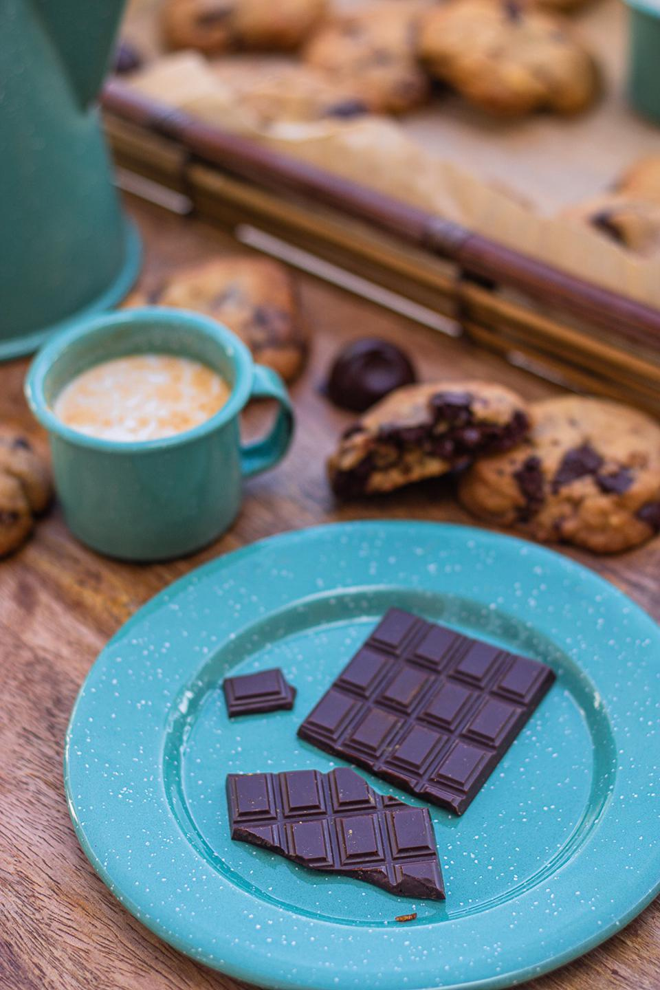 A blue plate with a bar of dark chocolate, with several chocolate chunk cookies and a mug of a milk chocolate next to it
