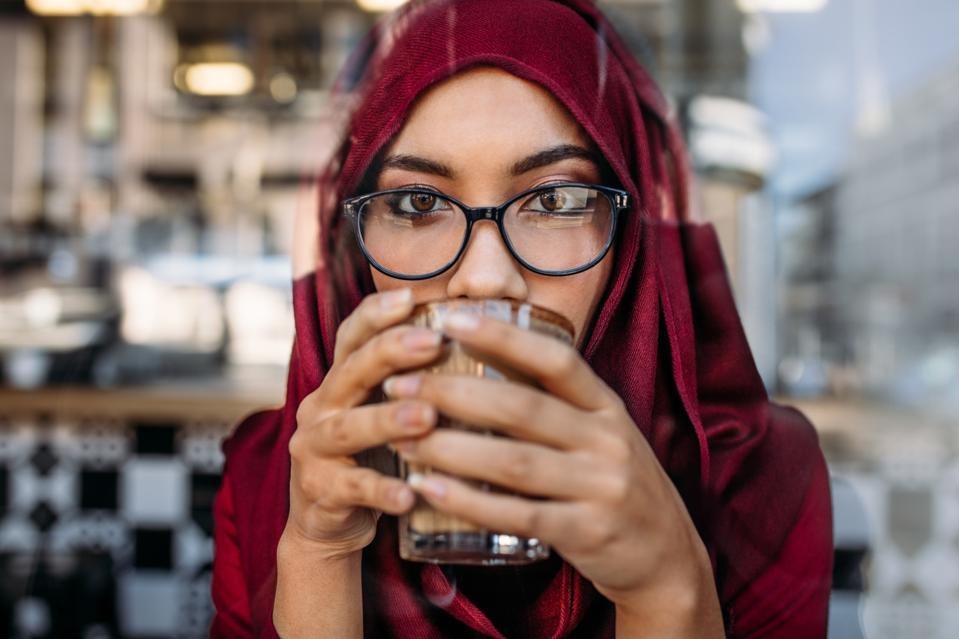 Muslim woman having coffee at cafe