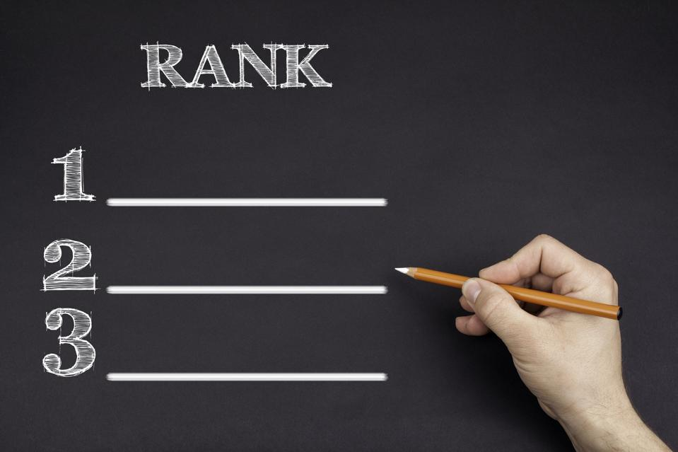 Hand with a white pencil writing drawing up a ranking table.