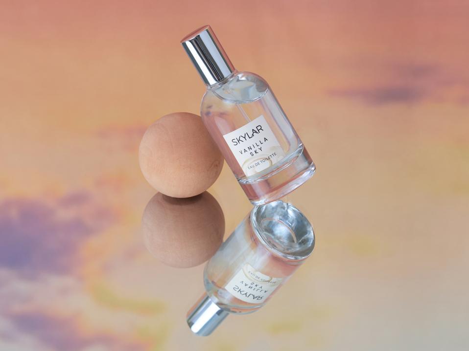 A bottle of Skylar Vanilla Sky perfume against a peach pink sunset.