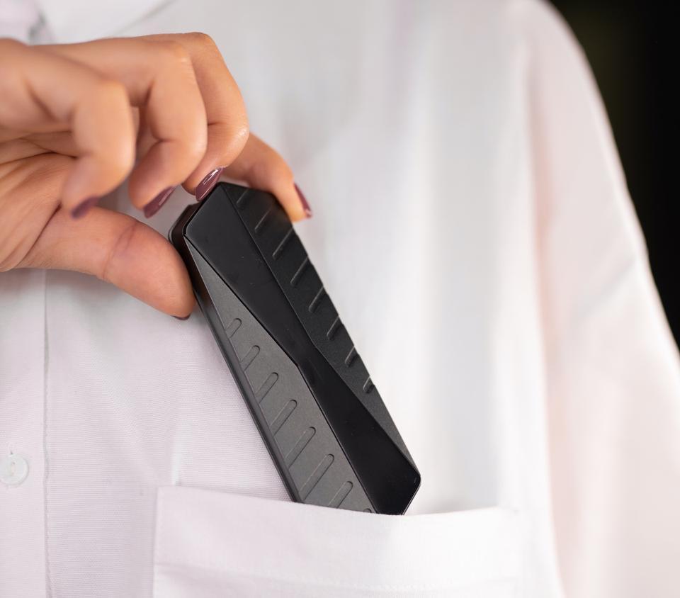 Hand putting GigaDrive into a shirt pocket