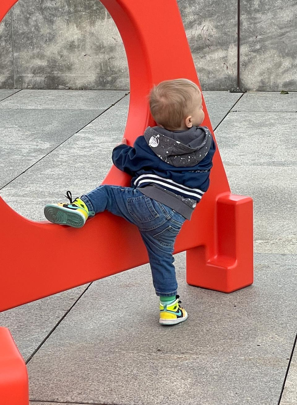 Child crawling around the base of the installation