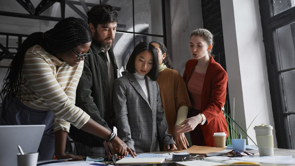 An image of a diverse work team collaborating on a project.