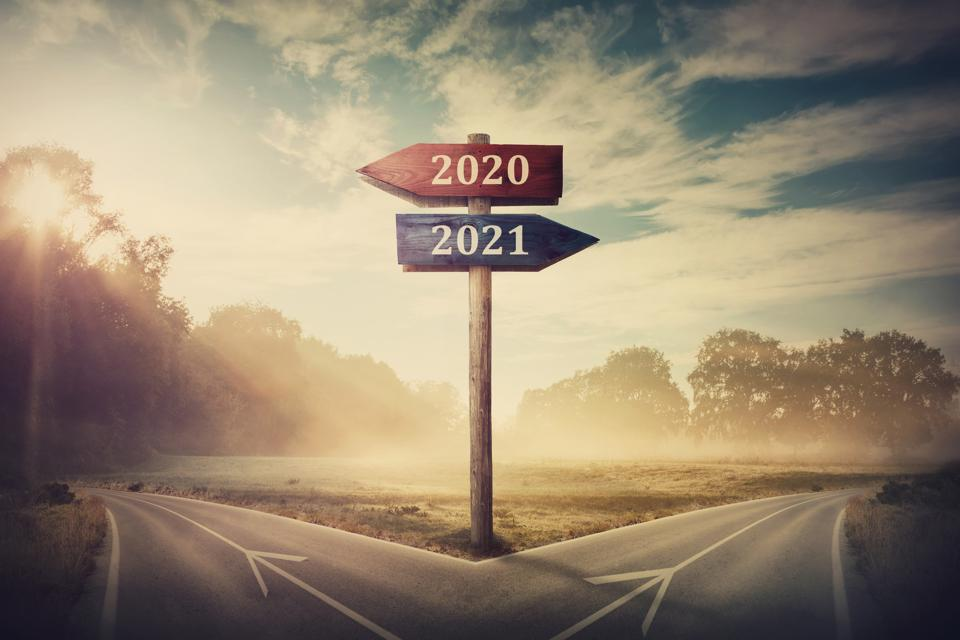 Surreal scene with a split road and signpost arrows showing two different courses, left and right, past and future, old 2020 and the new 2021 year direction to choose. Life decision, choice concept.