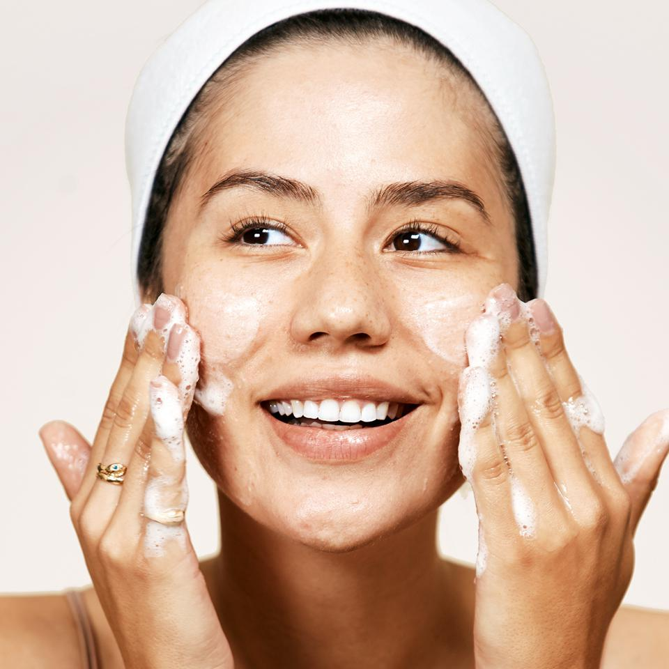 A smiling woman rubs cleanser into her face.