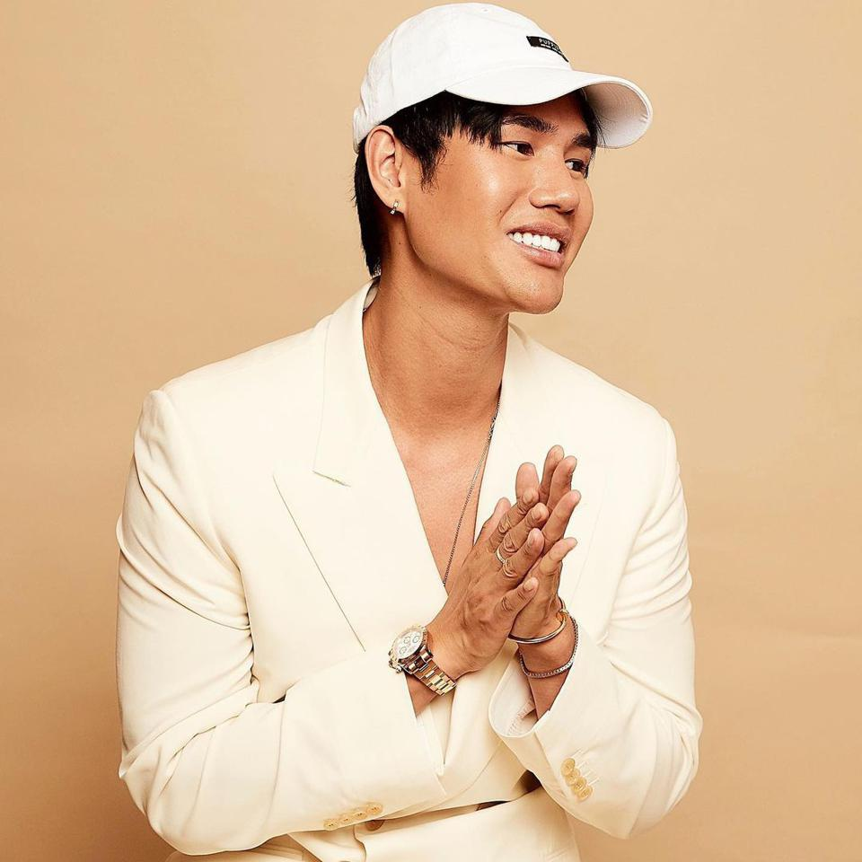 Patrick Ta, makeup artist and founder of Patrick Ta Beauty smiles in a white cap and white blazer.