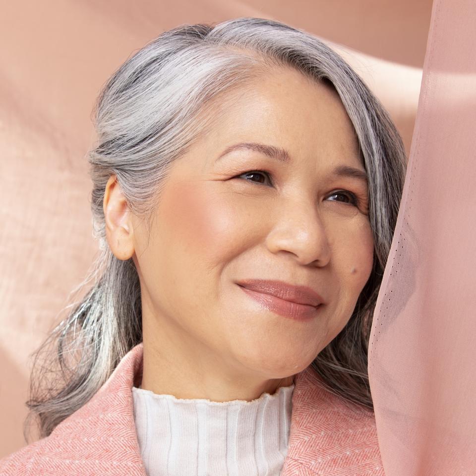 An woman in a pink blazer wears the Em Cosmetics Venetian rose blush.