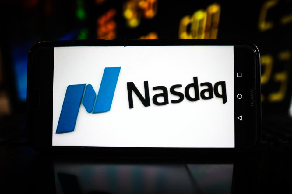 In this photo illustration a Nasdaq logo seen displayed on a...