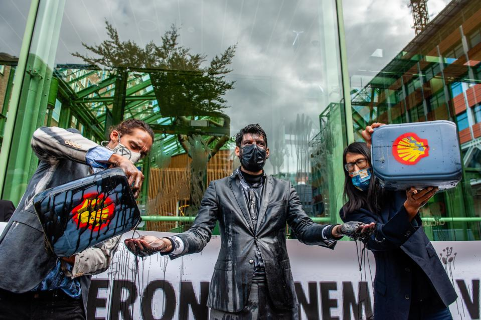 Climate activists protest Shell with suits soaked in fake black oil in The Hague.