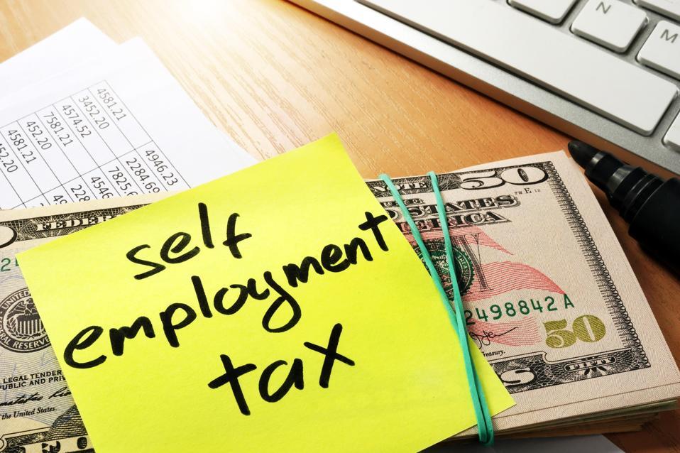 Self employment tax written on a memo stick.
