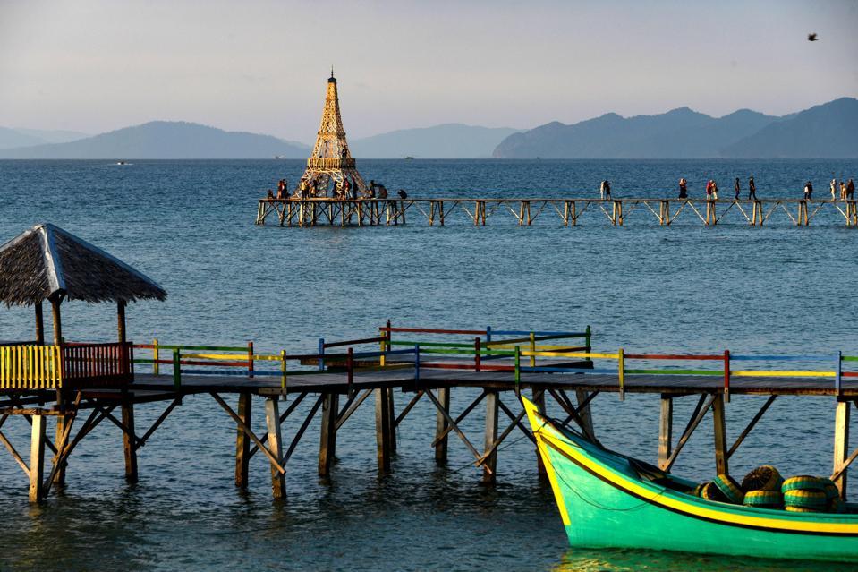 People walk on a pier at Lhokseudu beach, Aceh province, Sumatra