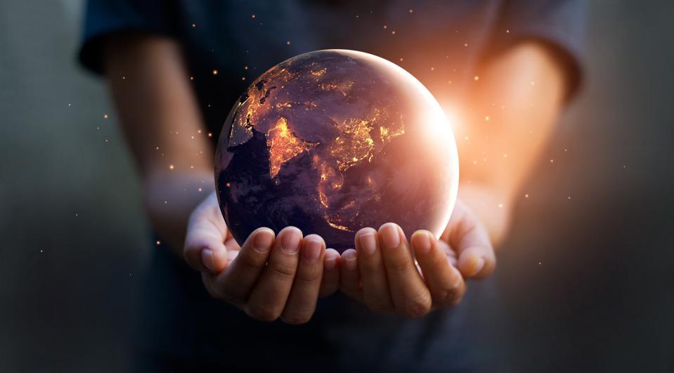 Hands holding an illuminated globe