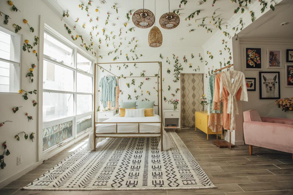 Gold canopy bed over a print rug in a room with flowers on the walls