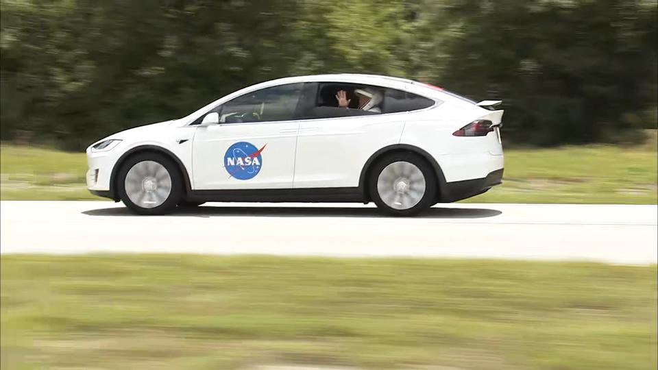 An astronaut waves out the window of a Tesla Model X.