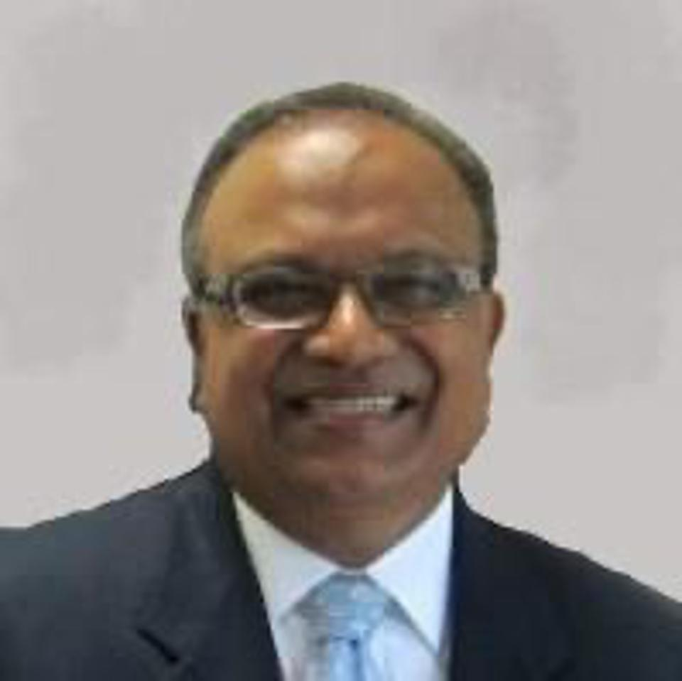 Trip Tripathy, middle-aged Indian man with short hair and glasses, smiling at camera.