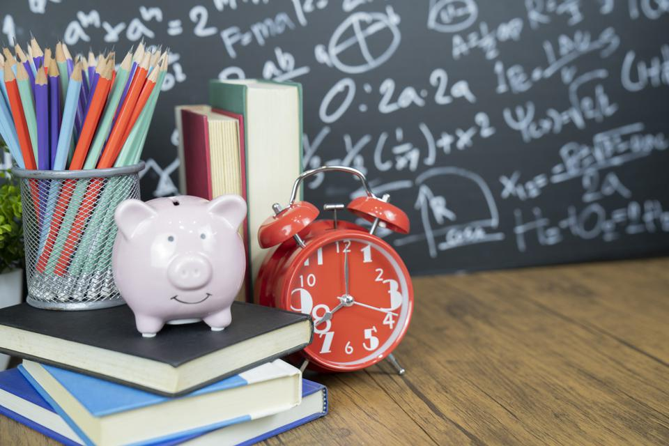 Desk with a piggy bank, alarm clock and pencils before a chalkboard filled with equations.
