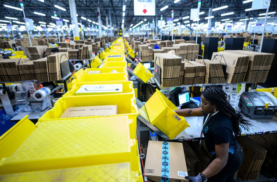A woman works at a packing station at an Amazon fulfillment center.