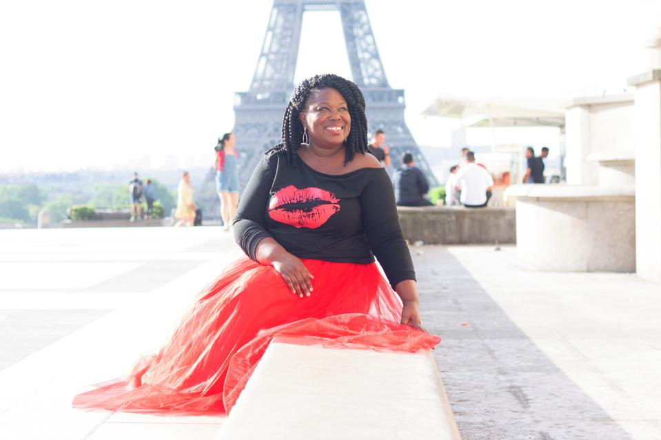 A photo of a woman with a red skirt and black top sitting on a stair with the Eiffel Tower in the background.