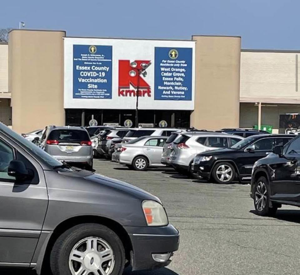 Photo of cars in the parking lot of a former Kmart that now serves as a vaccination site.