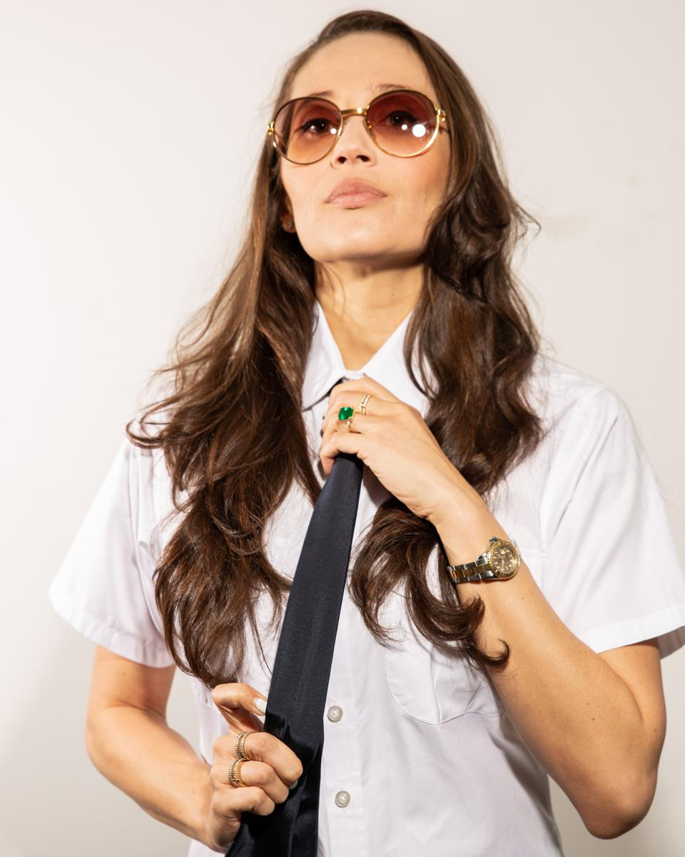 Raquel Horn stands alone wearing a tie and sunglasses