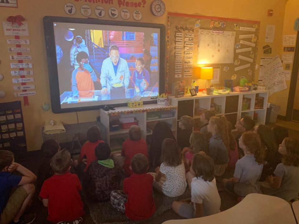 Generation Genius on a large screen in a classroom with 20 young kids watching.