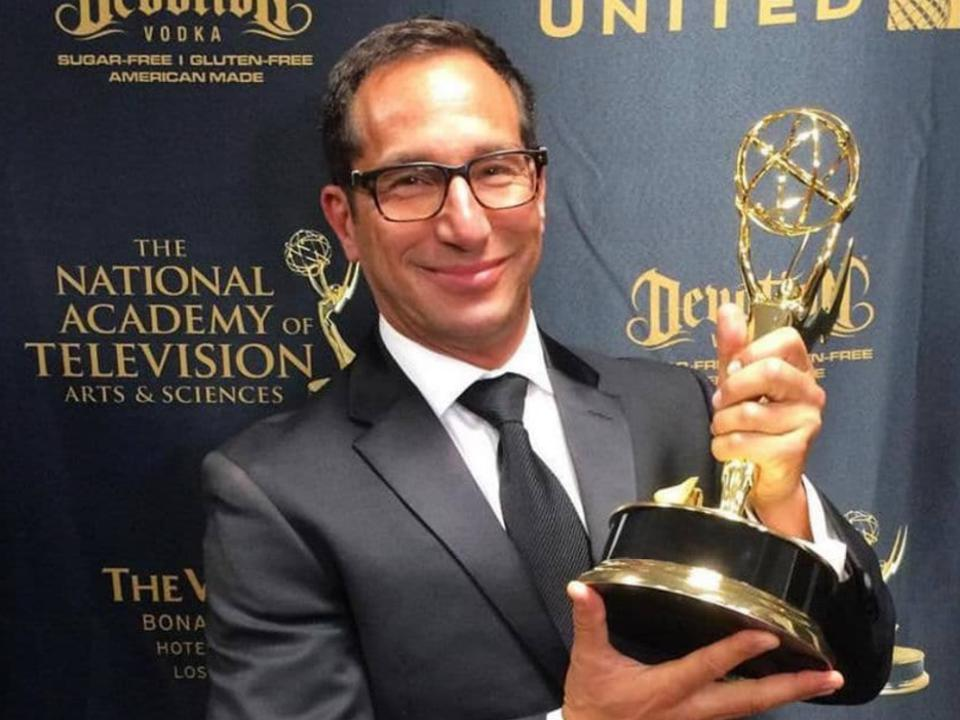 Rollman poses with an Emmy statue in his hand.