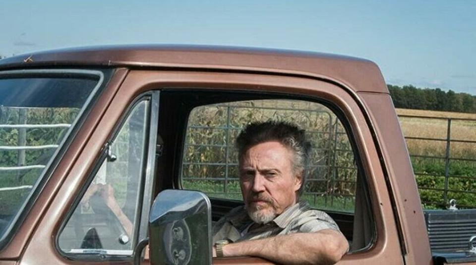 Christopher Walken sits in a truck with the window down. Behind him is a corn field.