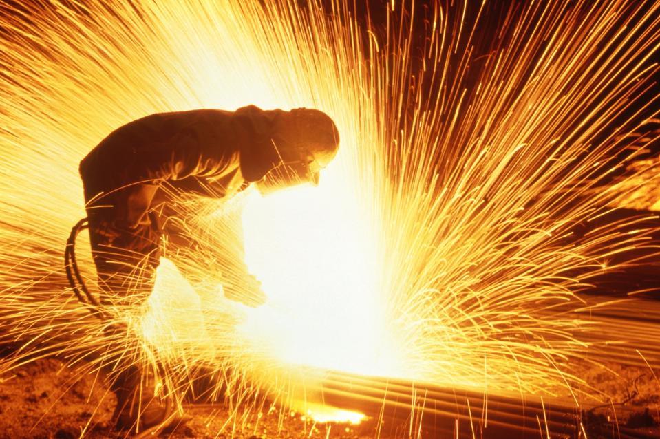 Man Welding In Factory Wearing Protective Helmet