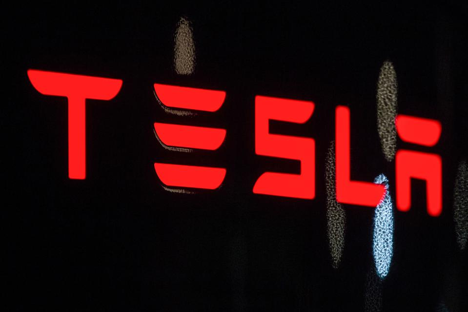 In this photo illustration, the Tesla logo seen on a...