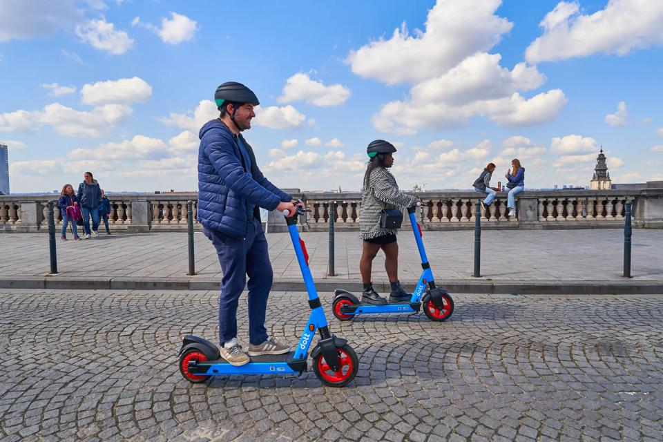 Man and woman riding e-scooters on the street.