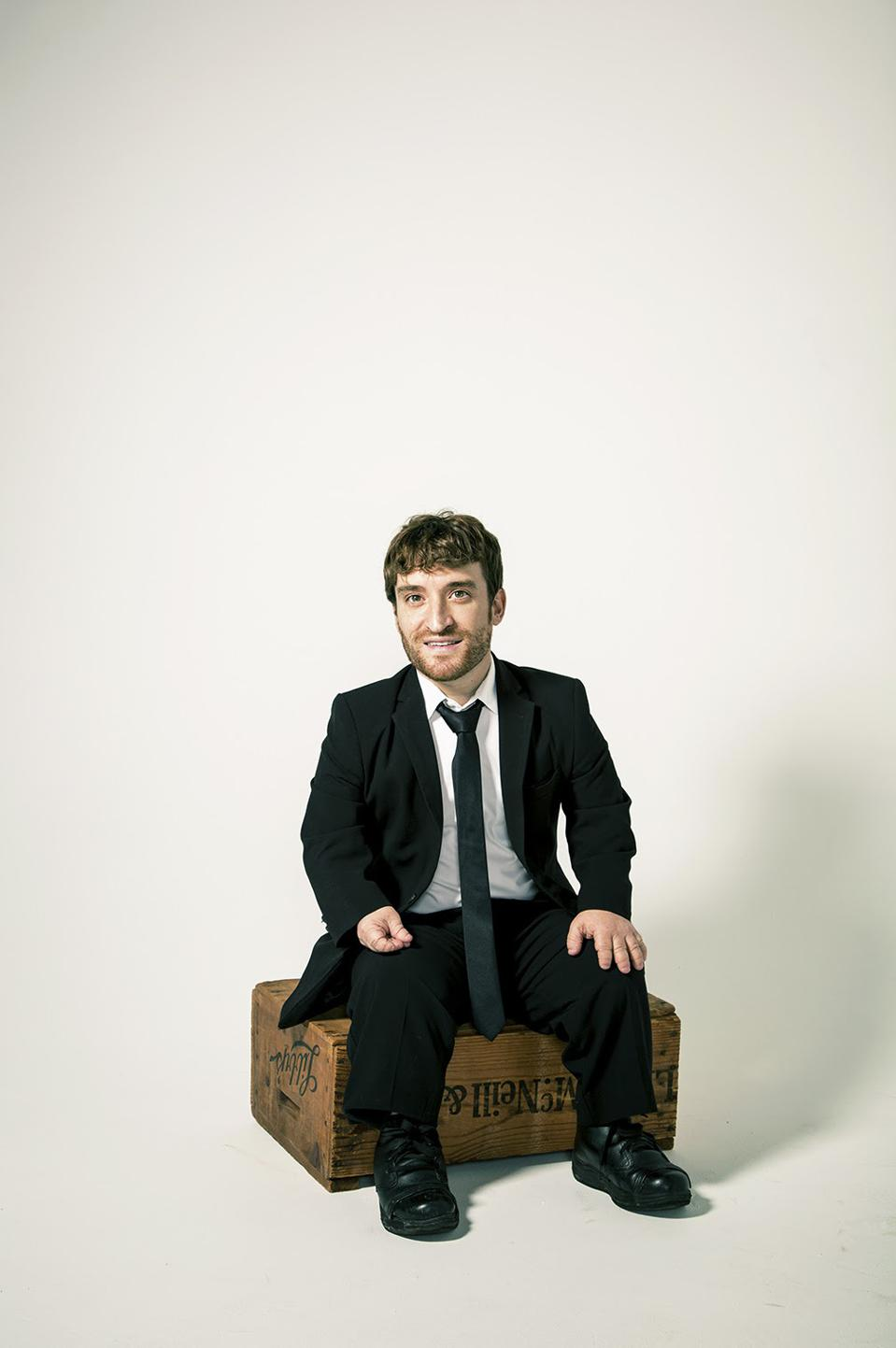A white man, who is a little person, sits on a wood box wearing a suit.