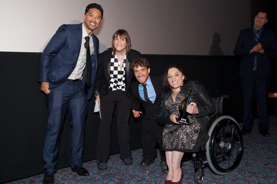 An asian man, white woman, white man who is a small person, & white woman in a wheelchair.