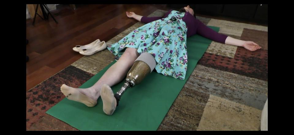 A white woman with a prosthetic leg lays on a green mat on the floor.