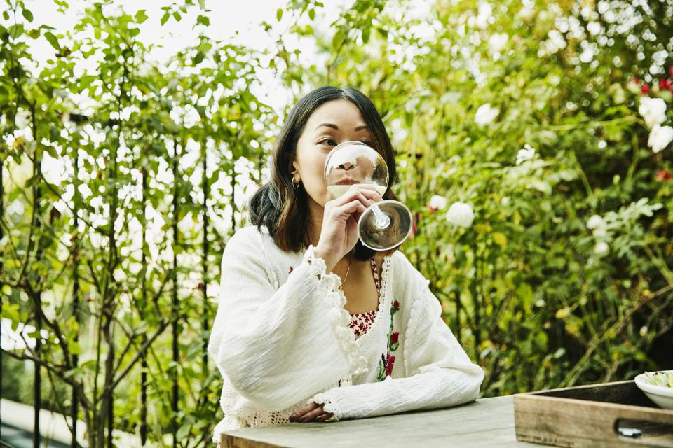 Woman drinking wine at table in backyard