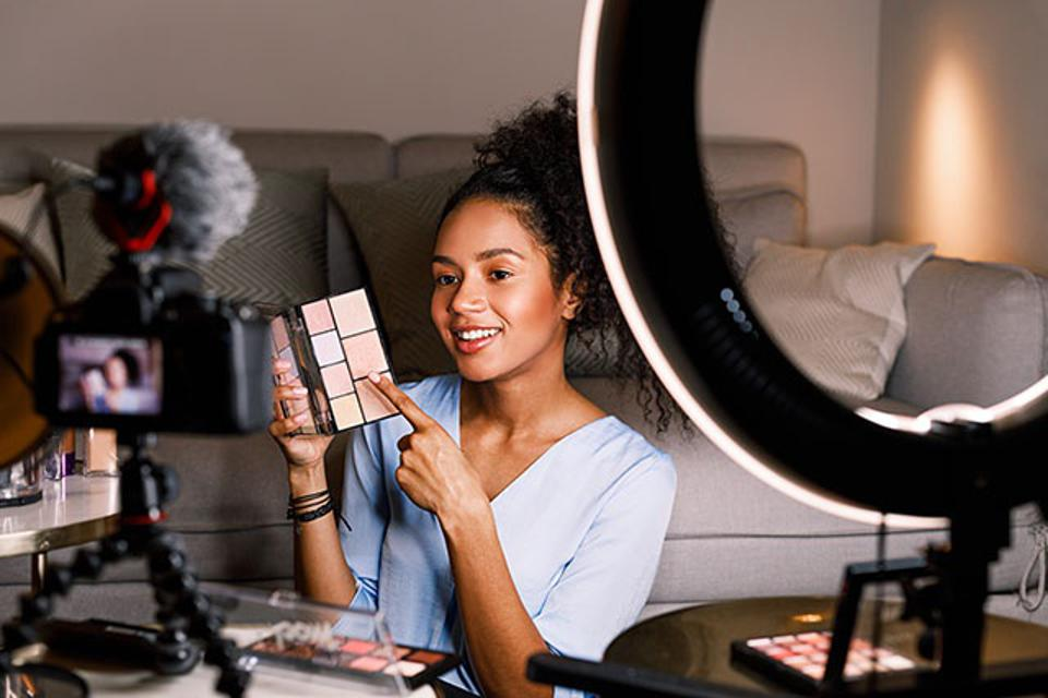 Smiling Young Woman Showing Beauty Product While Filming At Home